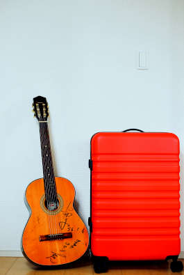 A red suitcase sits next to a guitar with signatures