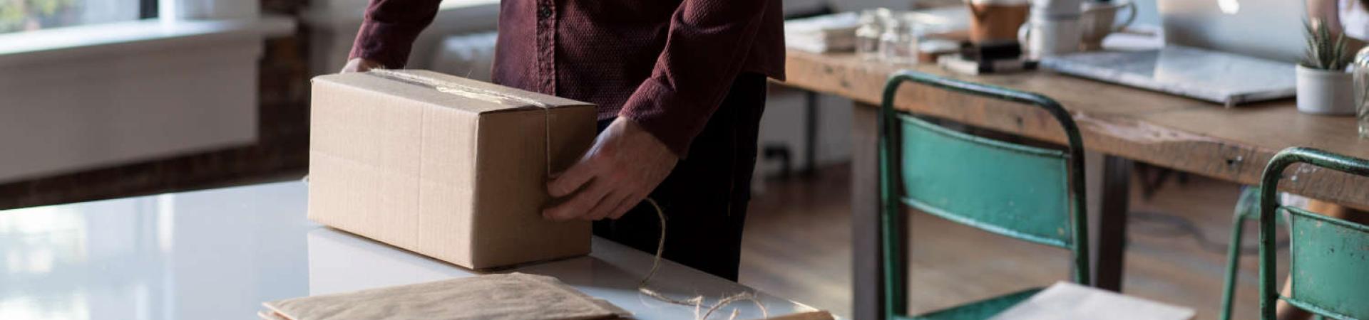 Man in an office preparing brown envelopes and cardboard box for shipping