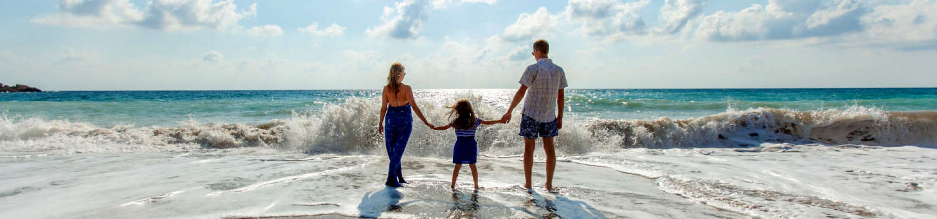 A child holds their parents hands while standing at the edge of the water at the beach